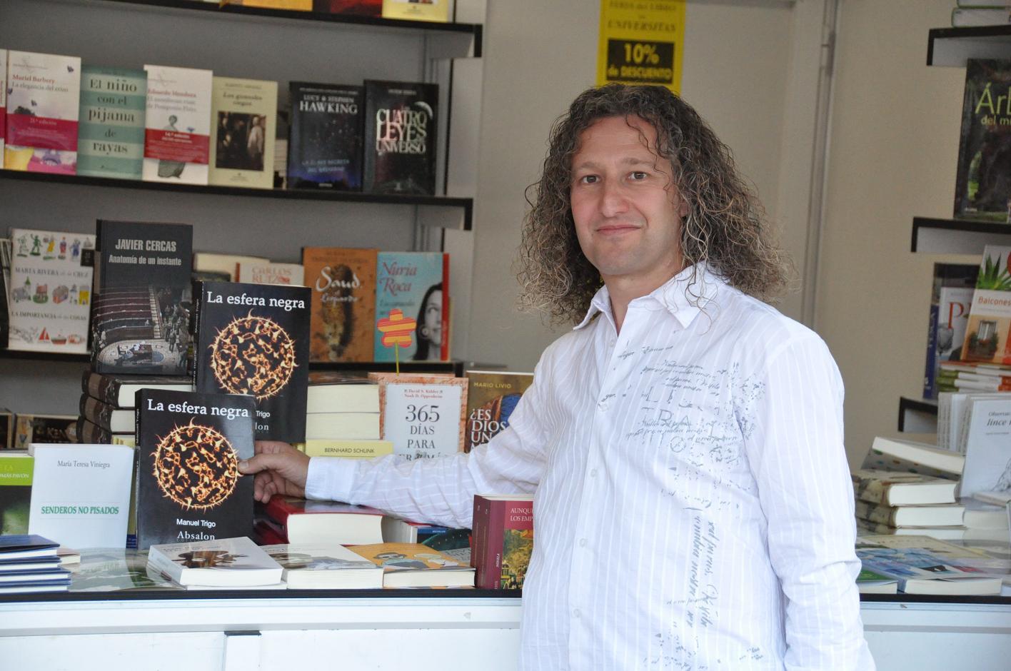 """Manuel Trigo con su novela """"La esfera negra"""" en una de las casetas de la Feria del LIbro de Badajoz."""